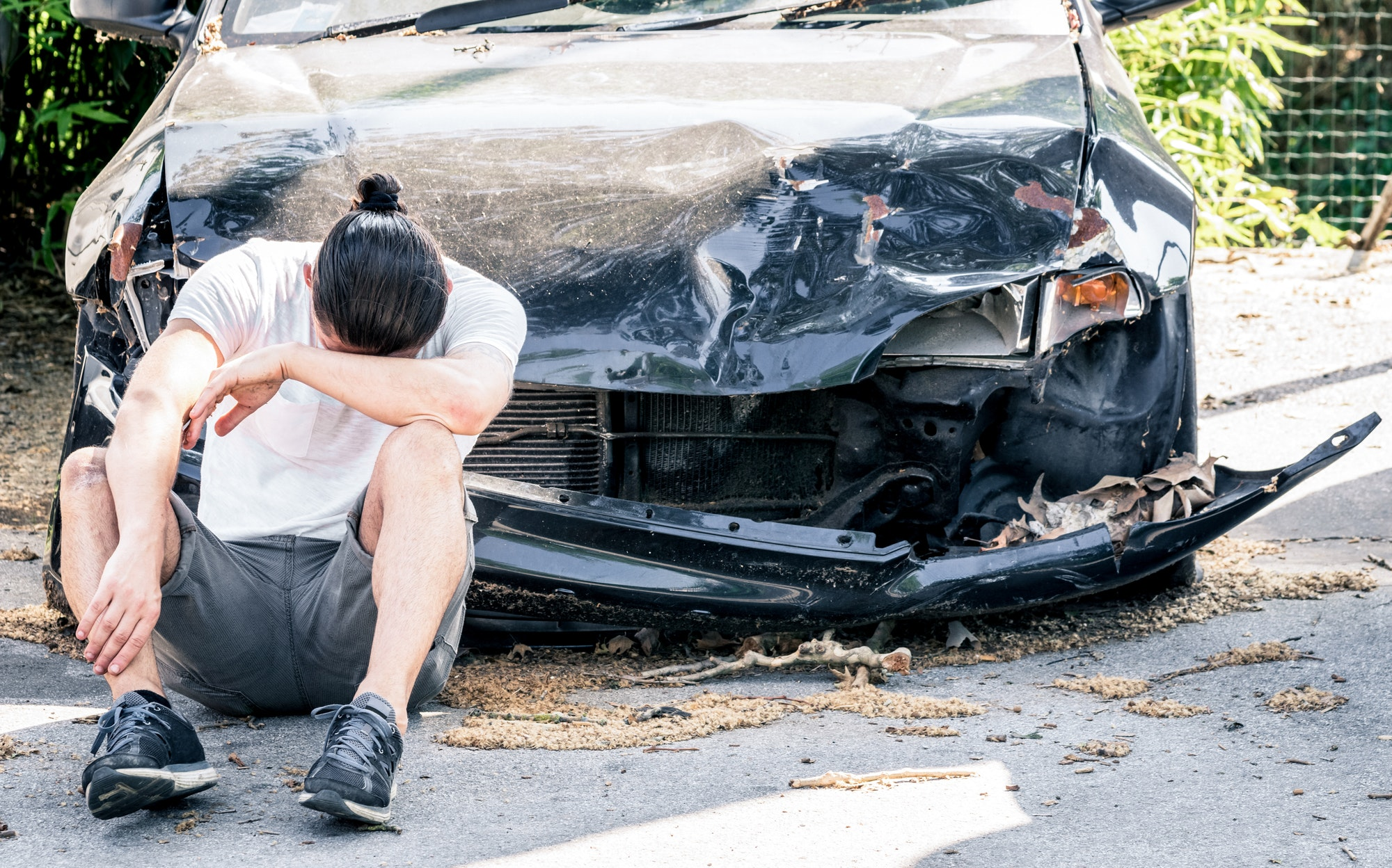 Man crying on his old damaged car after crash accident