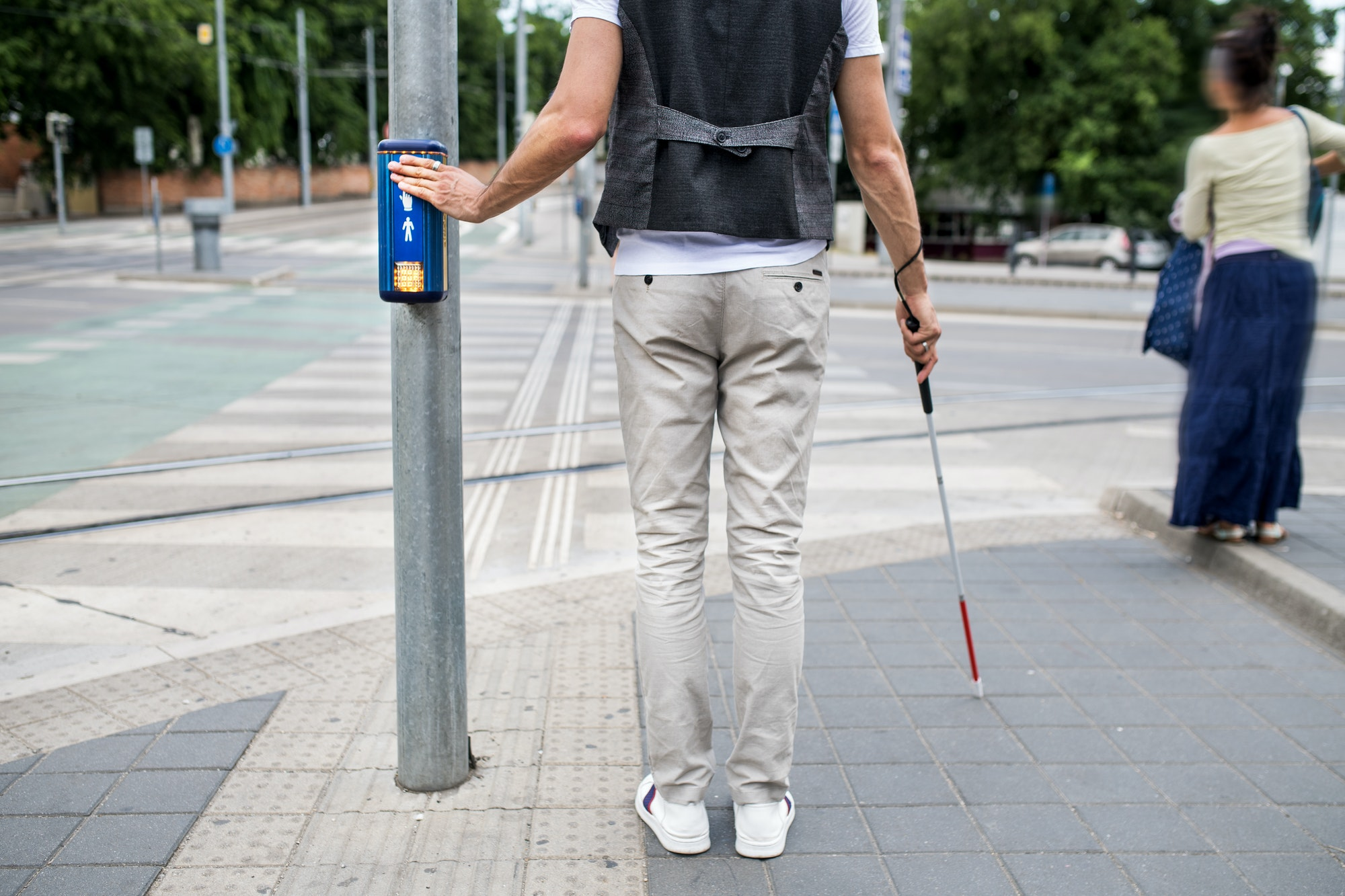 Midsection of blind man with white cane at pedestrain crossing in city.